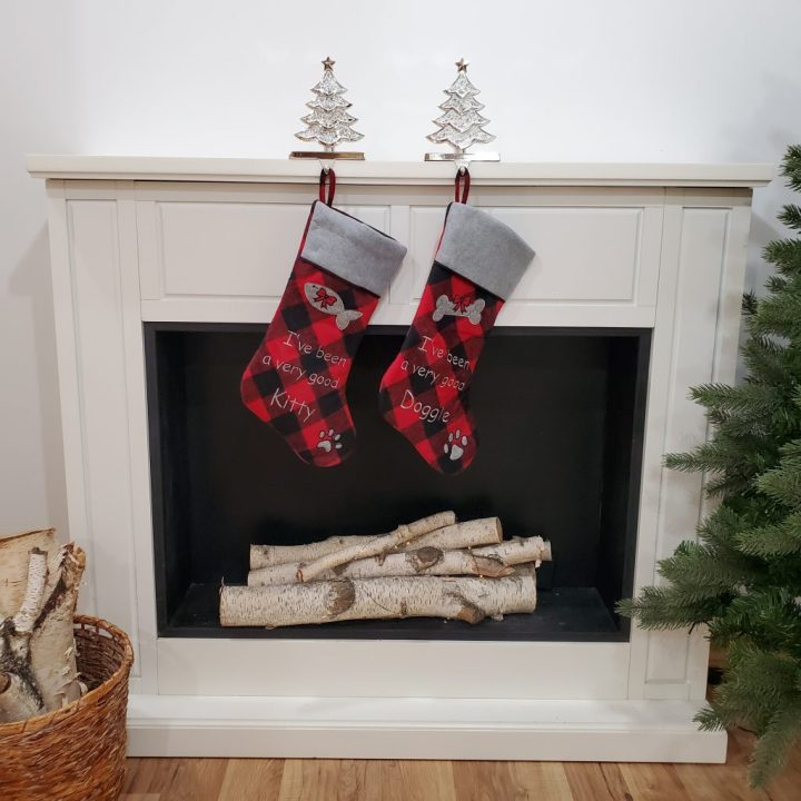Buffalo plaid Good Kitty and Good Doggie personalized stockings hanging from a mosaic Christmas tree stocking hanger on a white fireplace with birch logs in the fireplace.
