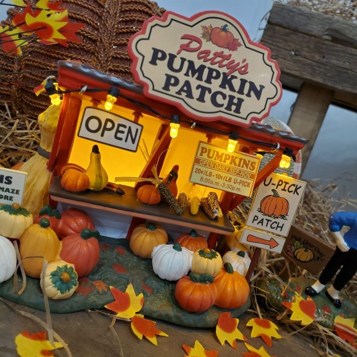 Decorating for fall with Department 56 with a closeup of lighted Patty's Pumpkin Patch on top of vintage cheese box.
