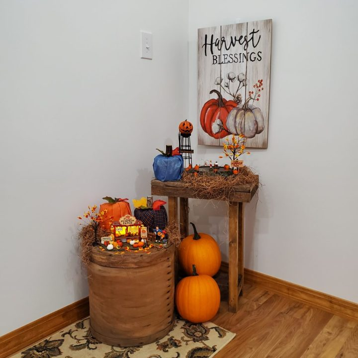 Decorating for fall with department 56 with Harvest Blessings wall art with Halloween Water Tower, Animated Pumpkin Patch and blue glitter toilet paper roll pumpkin on barn wood side table. Patty's Pumpkin Patch with an orange and an orange/navy/sky blue plaid toilet paper roll pumpkin on a vintage cheese box. One real pumpkin sits on the bottom shelf of the table and the other is on the floor in front of it next to the cheese box.
