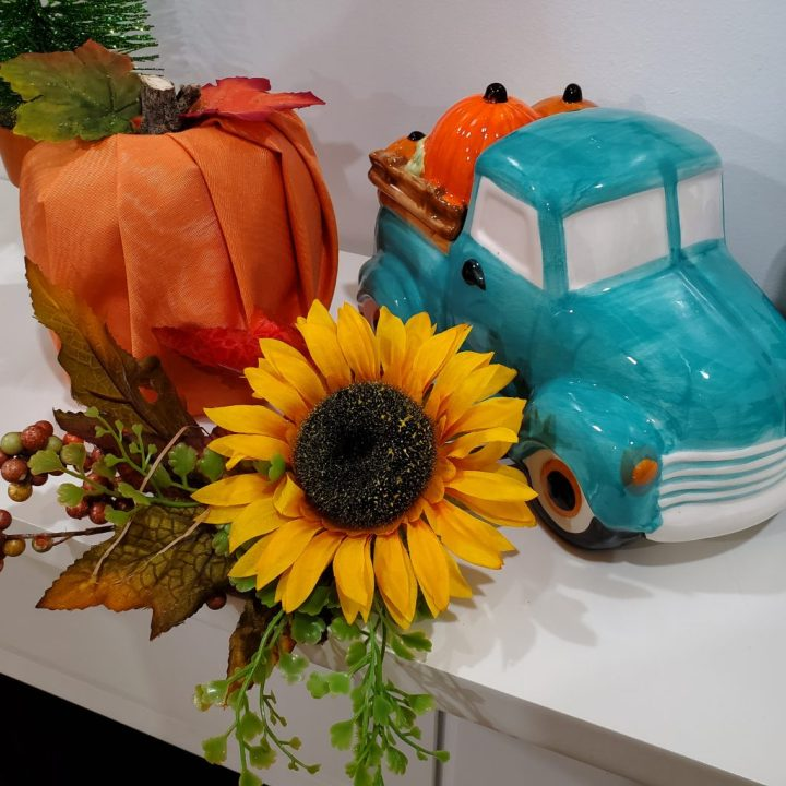 Closeup of orange DIY toilet paper roll pumpkin, sunflower spray, and blue harvest truck cookie/candy jar atop a white fireplace mantel for fall decorating.