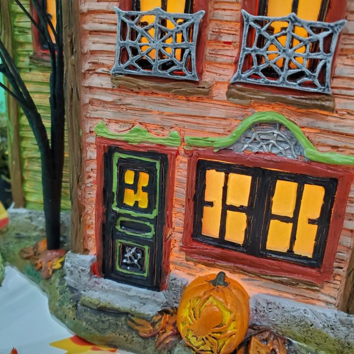 Closeup of Spider House showing spider web bars on the windows and as other architectural trim along with a pumpkin in front of the house carved into a spider for decorating for Halloween