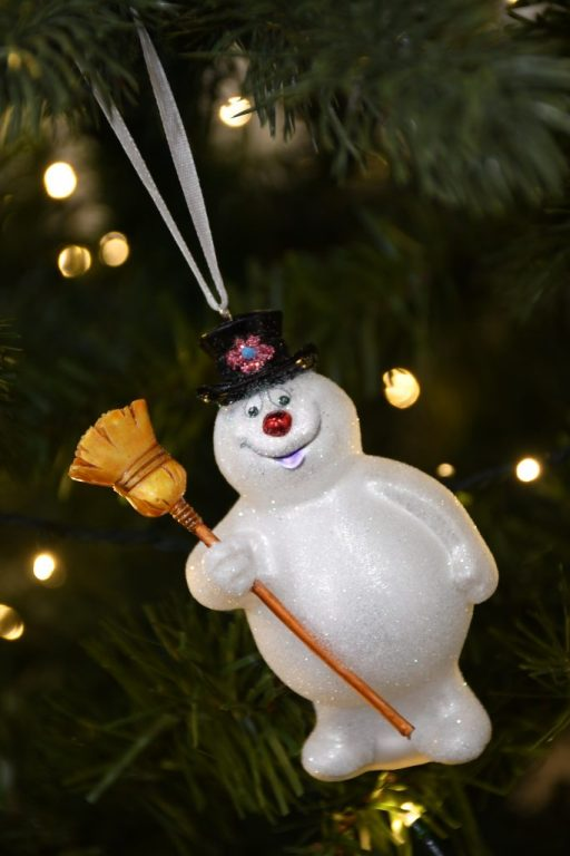 Frosty the Snowman glass ornament hanging on lighted Christmas tree