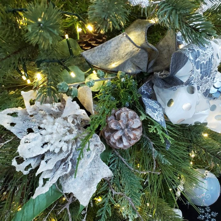 Gray poinsettia and ribbon evergreen unit/swag on Christmas tree as focal point for 2021 Christmas trends.