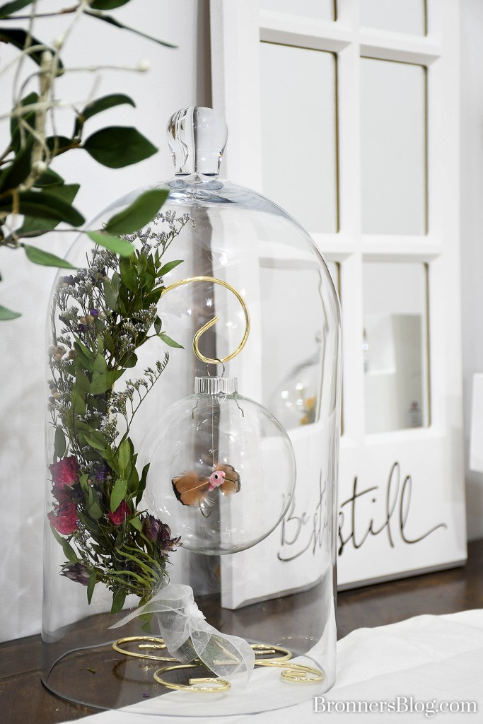 Dried flowers on an orament stand inside a glass cloche
