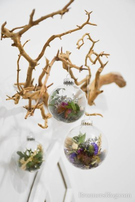 Dried flower ornaments hang from a Manzanita branch.