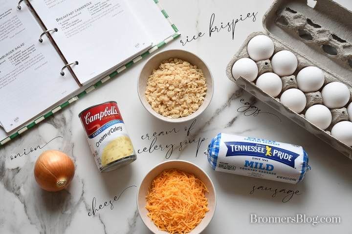 Bronner's breakfast casserole recipe ingredients (a yellow onion, can of cream of celery soup, cup of Rice Krispies, bowl of shredded cheddar cheese, tube of sausage, and eggs in carton) are laid out on the white and black granite table top with the recipe book open to the recipe.