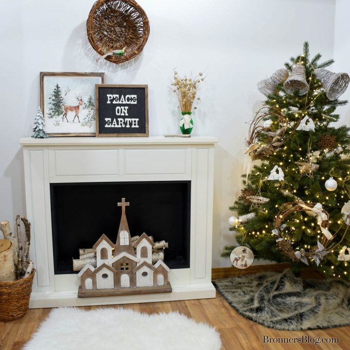 The tree is decorated with natural decor for Christmas along with the fireplace mantel that features natural artwork.