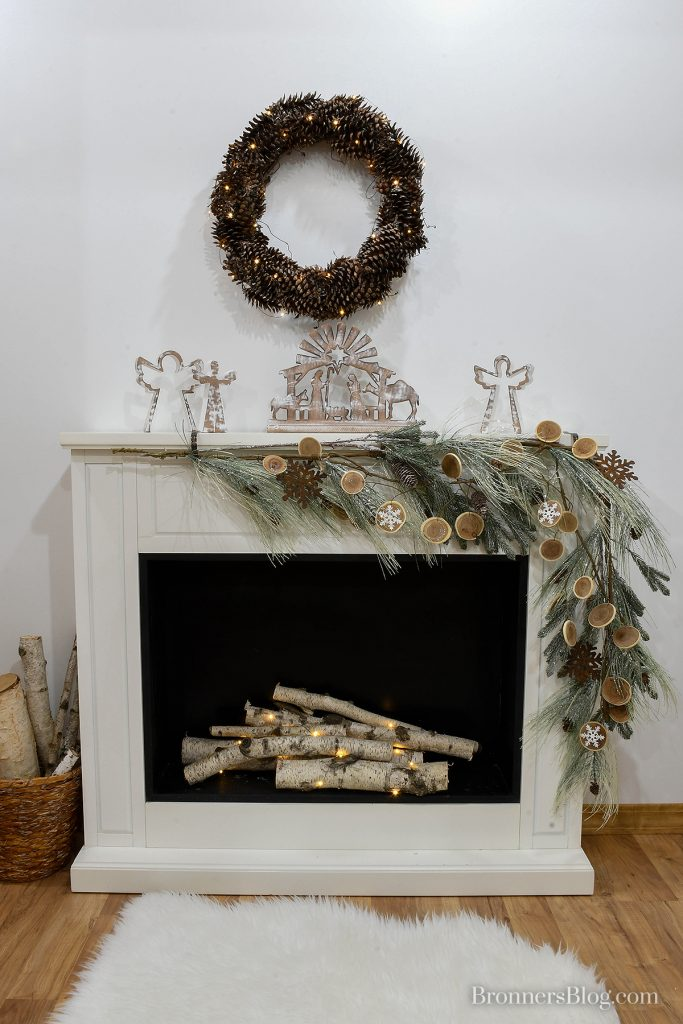 White fireplace with birch logs wrapped in battery-operated lights and white faux fur rug in front of it. White-washed nesting angels and Nativity on the mantle with a garland. Lighted pine cone wreath hanging above the fireplace provides sustainable decorations for Christmas.