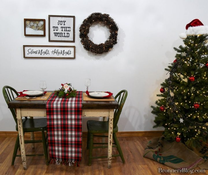 Wall decorated with pinecone wreath,, Joy to the World and Silent Night, Holy Night signs and 3D snowflake and snow shadow box. Table set with plaid runner, candle ring with Santa mug centerpiece, cork side of placemat, skating Santa plate, and Egyptian glass stemware.