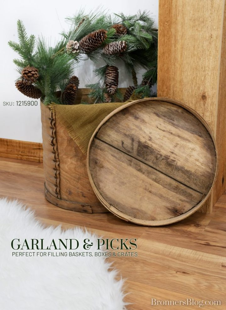 Wooden antique cheese box stuffed with faux pine garland with pinecones, sitting on wood floor next to faux white, fur rug.