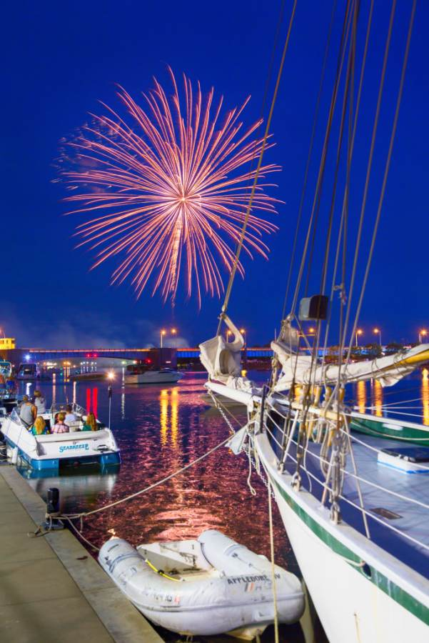 Fourth of July fireworks explode over bridge, river and boats in Bay City, Michigan