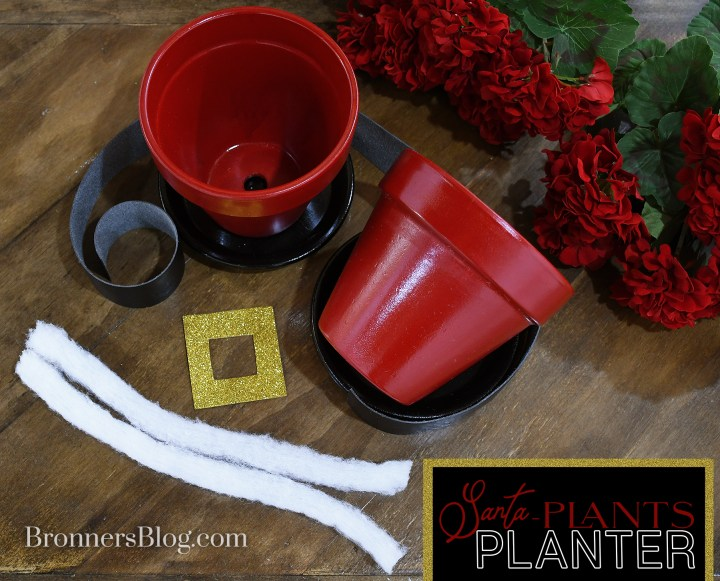 Materials gathered on the table to make DIY Santa Pants flower pots include clay pots and plates, black ribbon, glittery gold foam sheet, white batting and red silk geraniums