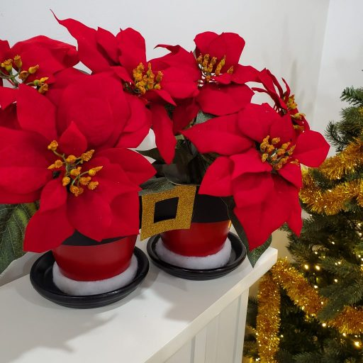 Red poinsettias fill the Santa pants flower pots at Christmastime.