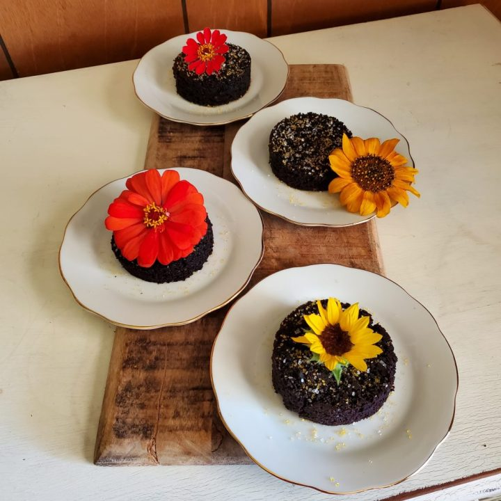 Black Magic cake rounds topped with flowers and individually plated atop a wood charcuterie board