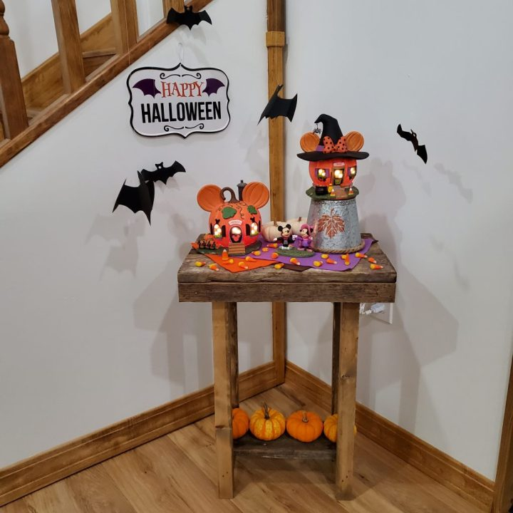 Mickey's and Minnie's Pumpkintown Houses are featured in a side table display with colored felt, candy corn and mini pumpkins.
