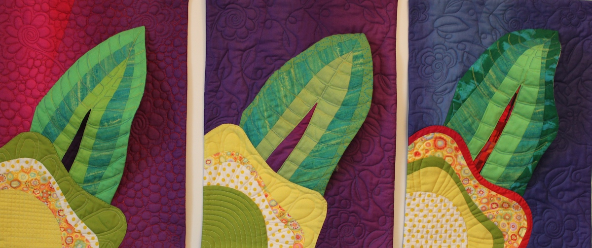 three leaf quilts of the stages of a butterfly metamorphosis by doris lovadina-lee, on display at the National Juried Show