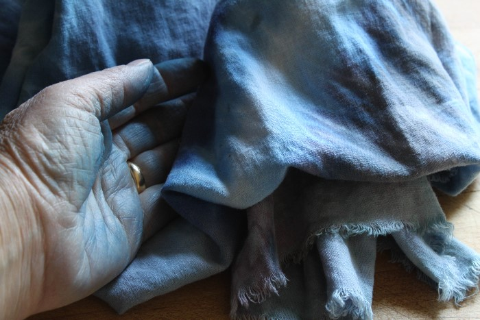 dyed hand holding blue hand dyed rayon linen scarf by doris lovadina-lee