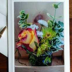 floral display in wooden holder photographed and on front of blank greeting note card