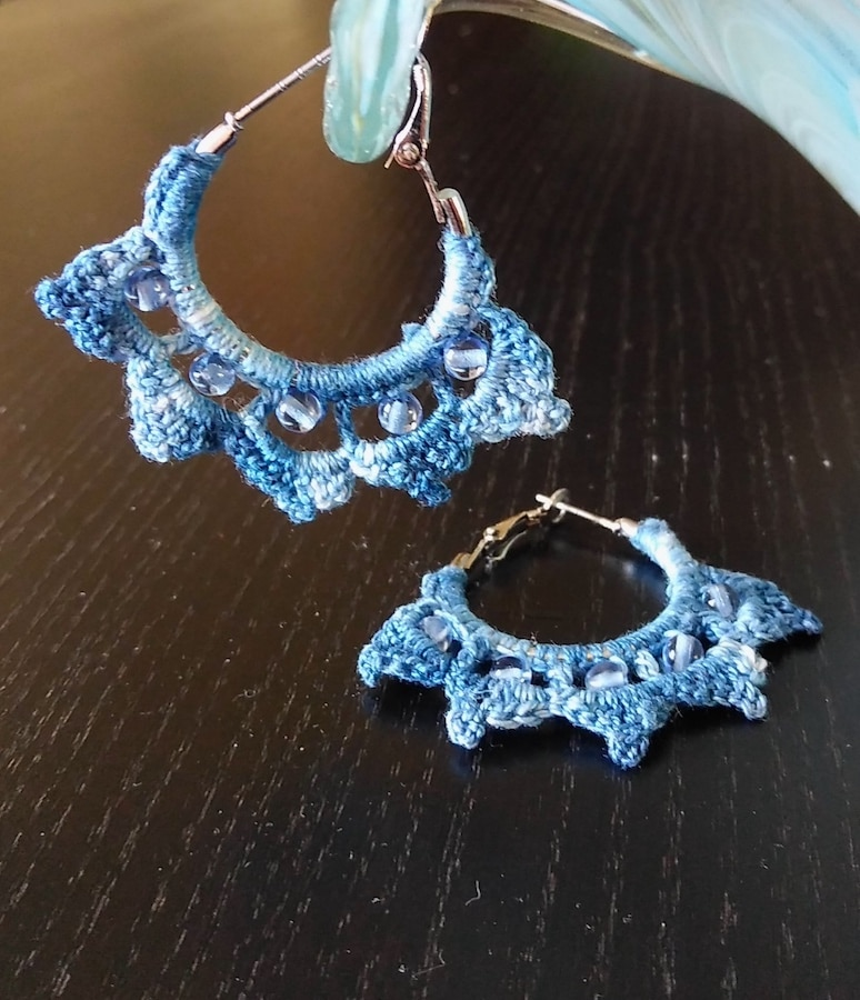 pair of indigo hoop crocheted earrings with blue glass beads on black surface
