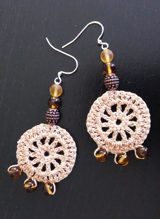 round crochet beige circle earrings with natural coloured beads on black background