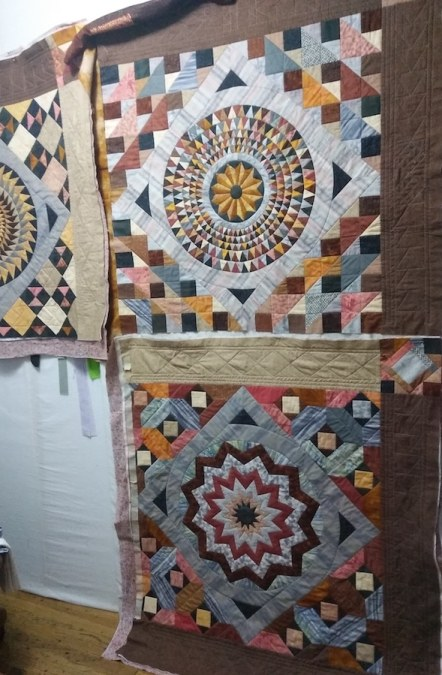 three large quilt bocks pinned to wall showing the machine quilting