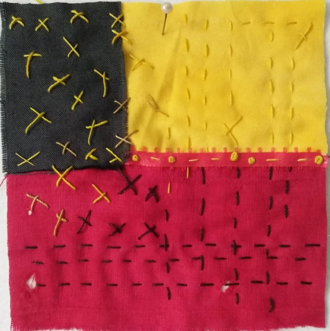 red, black and yellow fabric embroidered with black and yellow running and cross stitches and red silk ribbon with french knots