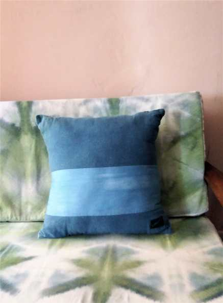 Indigo blue pillow with a lighter blue strip off centre on a green and white patterned chair