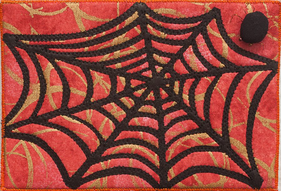 black spider on corner of a fabric postcard of a black spiderweb on printed orange cloth