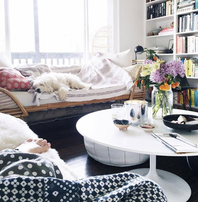 Cozy living room of Victoria Smith of SFGirlByBay with round white coffee table, wicker day bed and floor to ceiling bookshelves | Gather Goods Co