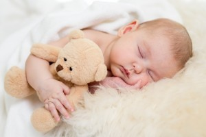 newborn baby sleeping on fur bed