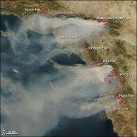 Le impressionanti colonne di fumo causate dai principali incendi (in rosso) lungo la costa della California del Sud. (credit: NASA)