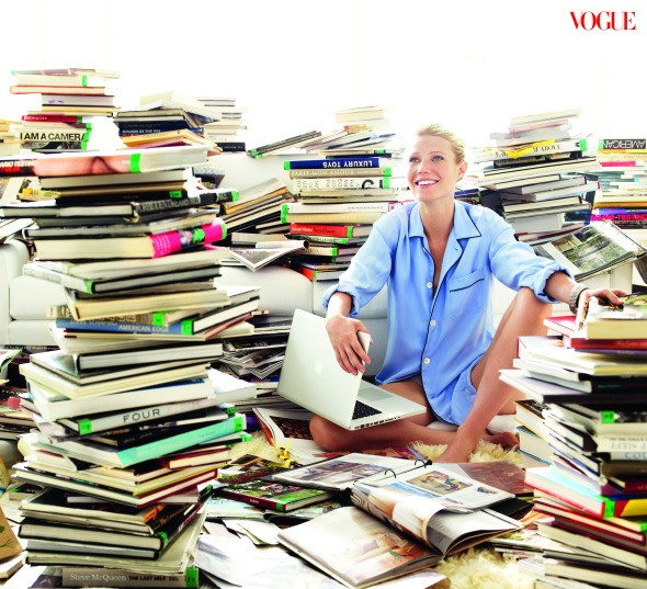 Gwyneth surrounded by, but not reading, books.