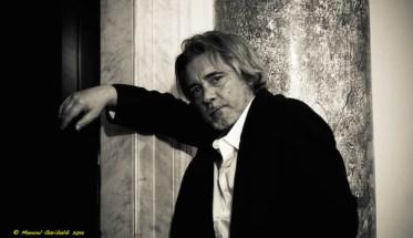 Il cantautore Max Manfredi appoggiato ad un muro