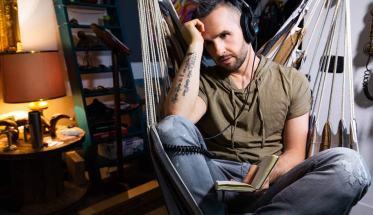 Il cantautore Roberto Casalino seduto su una amaca con in mano un libro