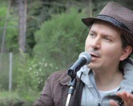 Roberto Cian cantautore con cappello davanti al microfono in un bosco