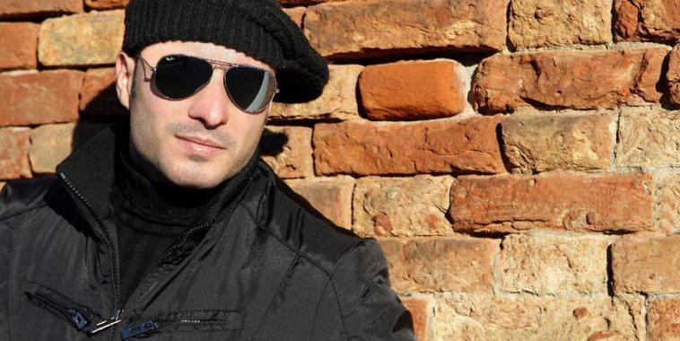 Nick Tempest vestito di scuro con un basco in testa appoggiato ad un muro di mattoni