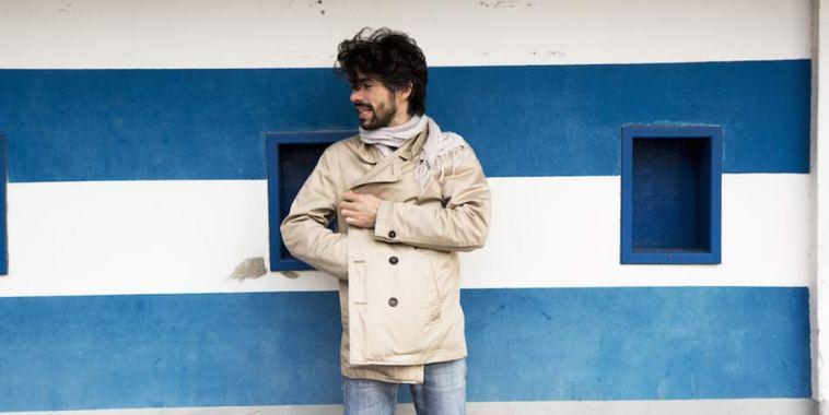 Luca Marino con il cappotto bianco su una parete a righe bianche e azzurre