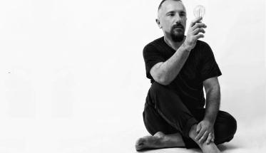 Simone Barotti seduto per terra con una lampadina in mano