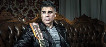 Toz Antonio Piretti seduto su un divano con la chitarra