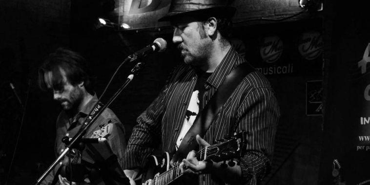 Francesco Luz con la chitarra a tracolla durante un live