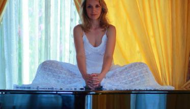 La cantante Paola Massoni vestita di bianco e seduta sopra un pianoforte