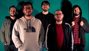 La band Under The Bed davanti ad uno sfondo verde