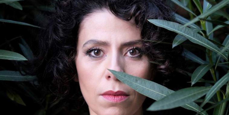 La cantautrice ChiaraBlue davanti ad un cespuglio verde