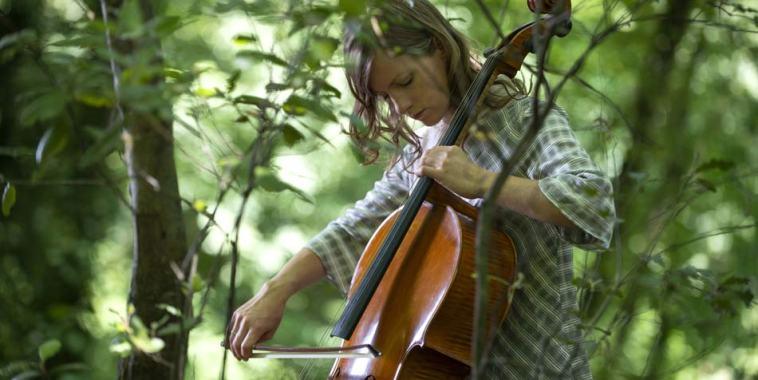 La violoncellista Naomi Berrill mentre suona in un bosco vicino agli alberi