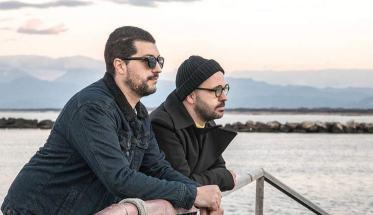 I due Humanoira appoggiati ad un parapetto mentre guardano il mare