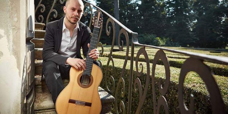 Alberto Mesirca seduto sui gradini di una scala all'esterno con la chitarra in mano