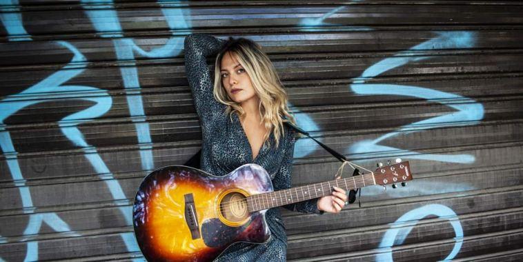 Chiara Castiglione con la chitarra davanti una serranda di negozio chiusa