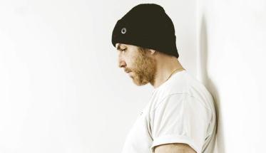 Silek rapper appoggiato al muro con berretto nero e maglia bianca