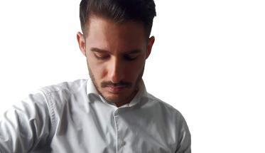 Salvo Ritz con camicia bianca e sguardo rivolto al basso
