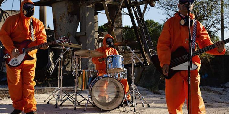 La band 10 HP con tute arancioni e maschera antigas